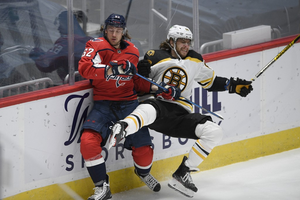 Washington Capitals left wing Carl Hagelin (62) and Boston Bruins right wing David Pastrnak (88) collide along the boards during the second period of ...