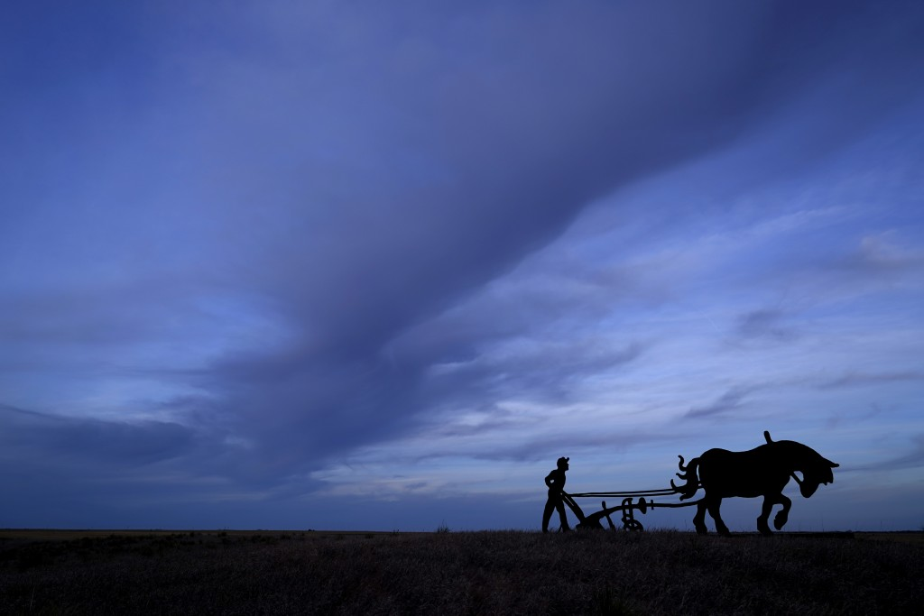 A steel cutout depicting a 19th century Black farmer rises from a field across the highway from the small community of Nicodemus, Kan., Thursday, Jan....