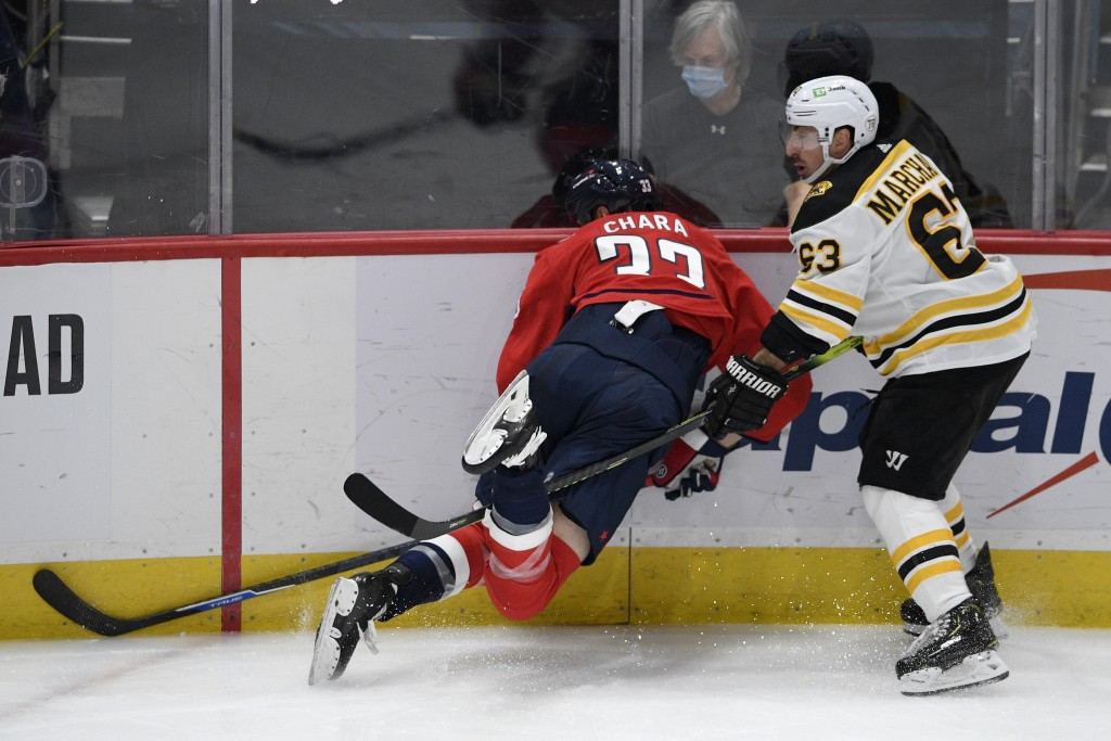 Washington Capitals defenseman Zdeno Chara (33) is tripped next to Boston Bruins left wing Brad Marchand (63) during the second period of an NHL hocke...