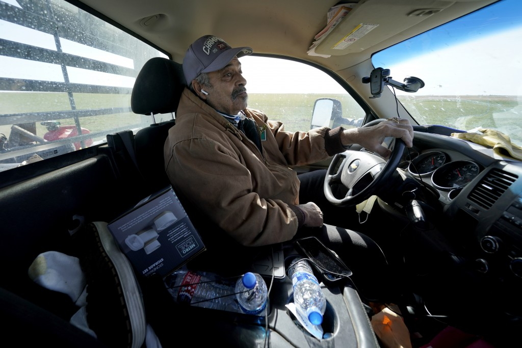 Rod Bradshaw drives down a dirt road as he goes to check on a field on his farm near Jetmore, Kan., Wednesday, Jan. 13, 2021. Bradshaw, who claims to ...