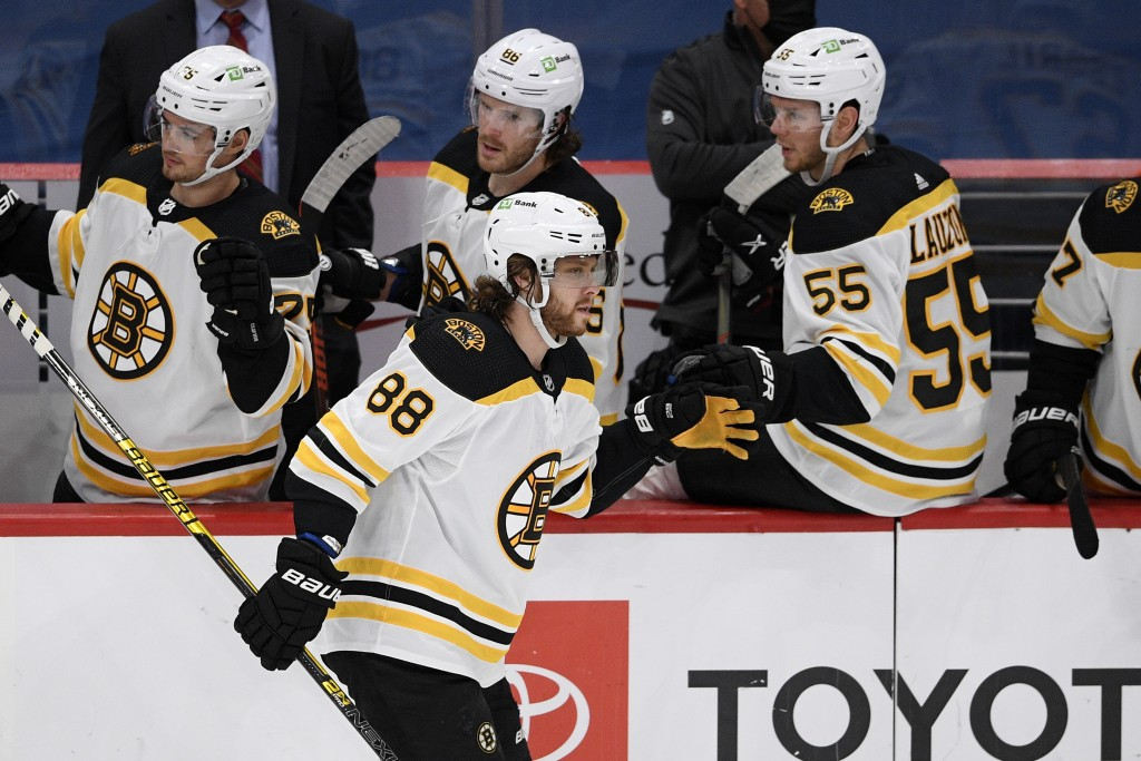Boston Bruins right wing David Pastrnak (88) celebrates his goal with the bench during the second period of an NHL hockey game against the Washington ...