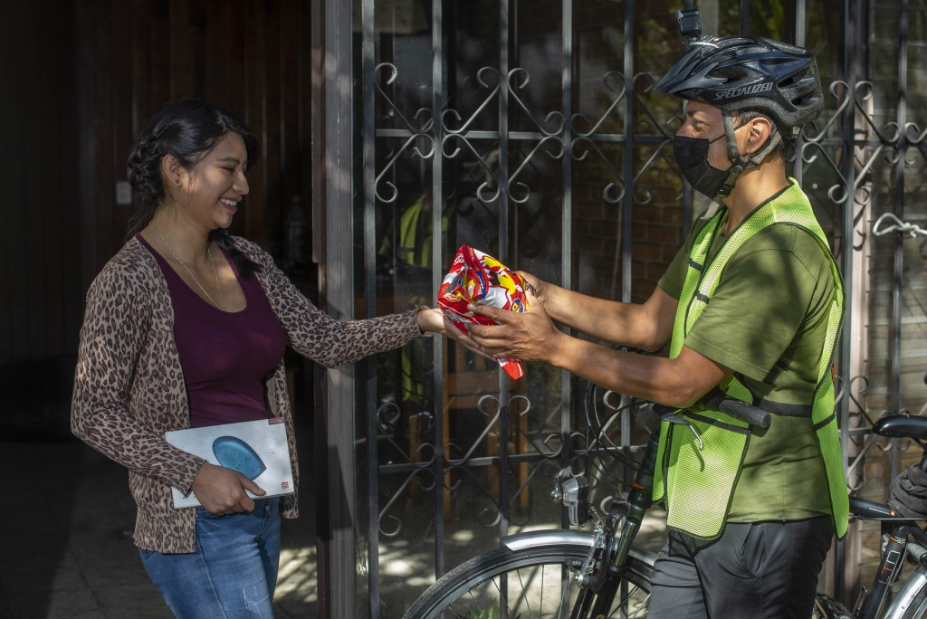 Ana Castillo trades 4 pounds of a cereal mix for a sociology book delivered by Bonifaz Diaz in Quetzaltenango, Guatemala, Saturday, Jan. 30, 2021. By ...