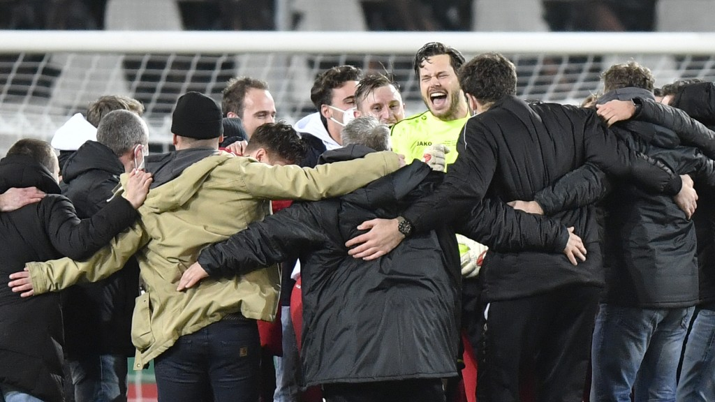 Essen's goalkeeper Daniel Davari, center right, celebrates with team mates at the end of the German Soccer Cup 3rd round match between RW Essen and Ba...