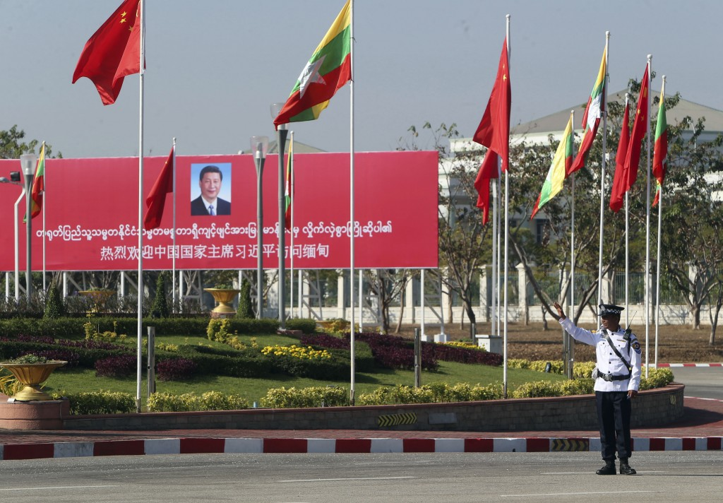 FILE - In this Jan. 17, 2020, file photo, a traffic police stands on a road as he clears a road near a welcoming billboard to Chinese President Xi Jin...