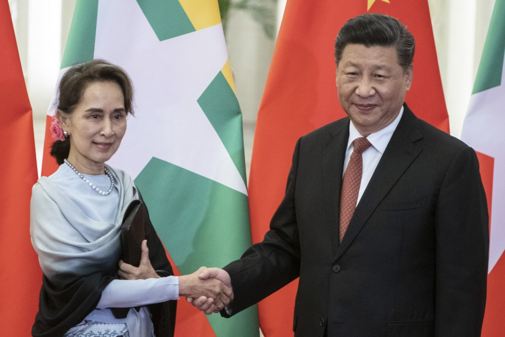 FILE - In this April 24, 2019, file photo, Chinese President Xi Jinping, right, shakes hands with Myanmar State Counsellor Aung San Suu Kyi at the Gre...