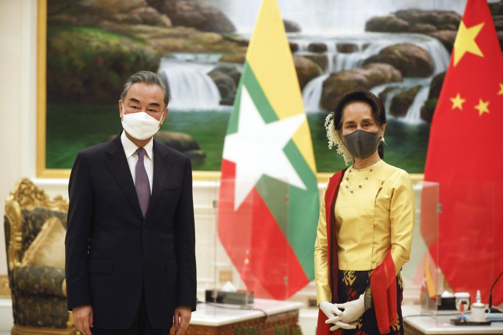 FILE - In this Jan. 11, 2021, file photo, Myanmar's leader Aung San Suu Kyi, right, and Chinese Foreign Minister Wang Yi pose for a photo, during thei...