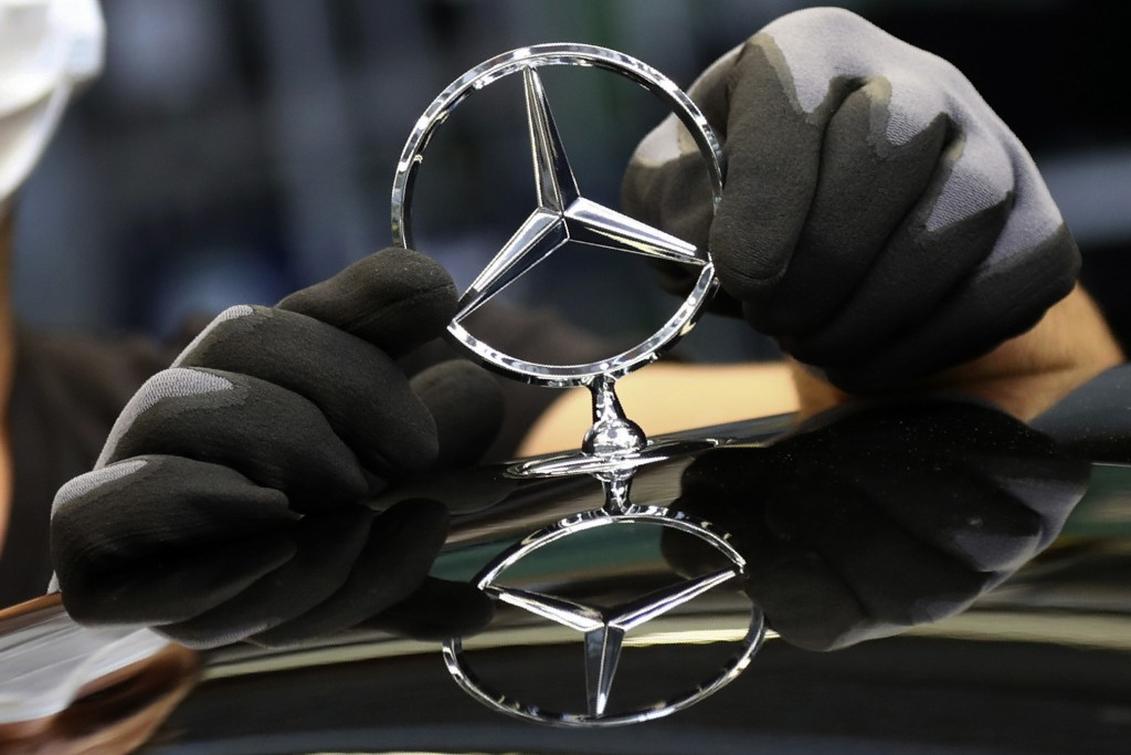 FILE - In this Thursday, April 30, 2020 file photo, an employee attaches a Mercedes emblem as he works on a Mercedes-Benz S-class car at the Mercedes ...