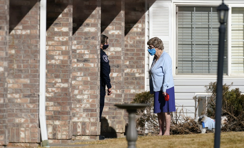 A police officer, left, talks to a resident as she walks her dog outside the front door of the Legacy Assisted Living at Lafayette care facility, Wedn...