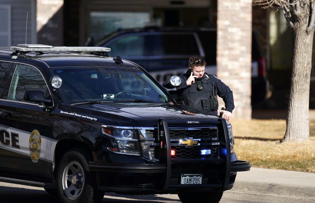 A police officer talks on a mobile device outside the Legacy Assisted Living at Lafayette care facility, Wednesday, Feb. 3, 2021, in Lafayette, Colo. ...