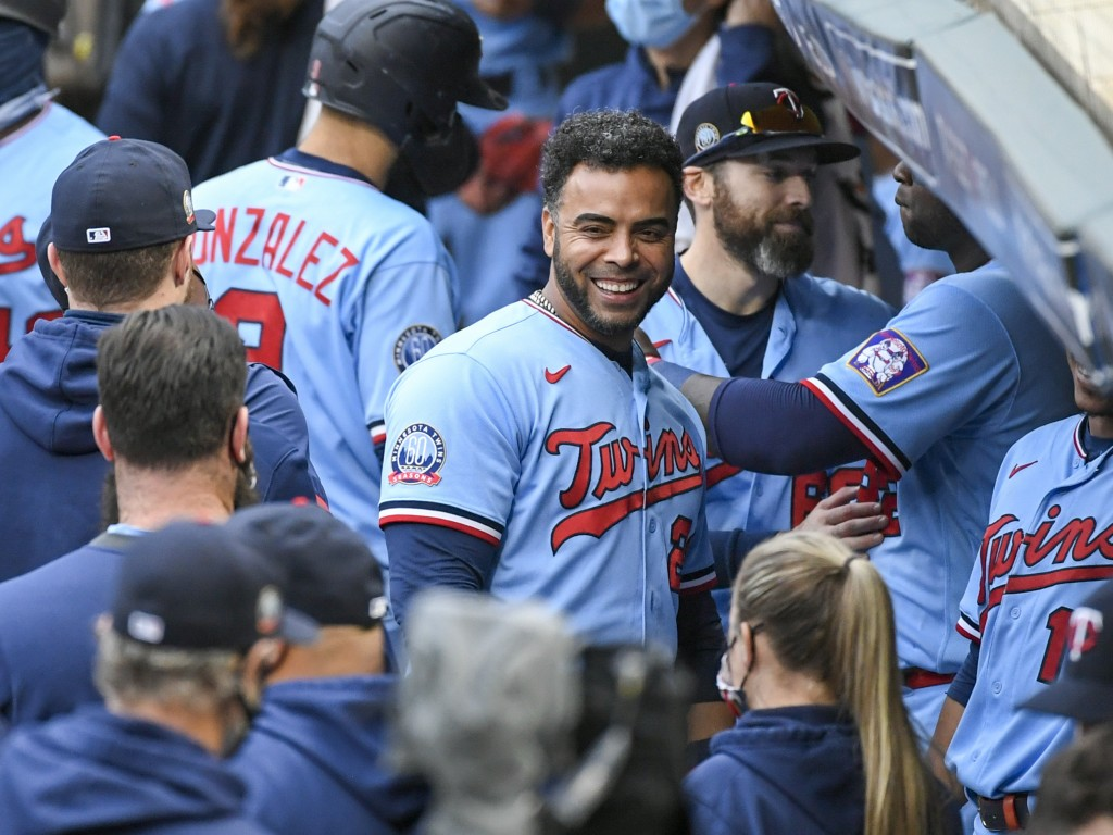 FILE - In this Sept. 27, 2020, file photo, Minnesota Twins' Nelson Cruz, center, smiles in the dugout after the Twins clinched the AL Central champion...