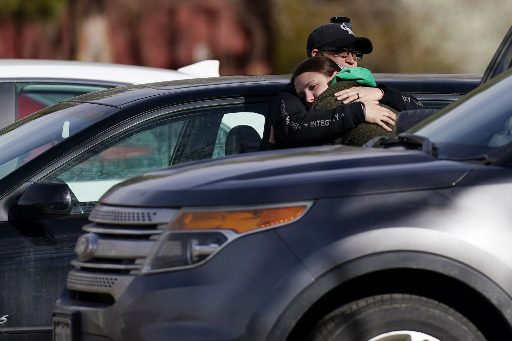 A couple embrace outside the Legacy Assisted Living at Lafayette care facility, Wednesday, Feb. 3, 2021, in Lafayette, Colo. A 95-year-old resident of...