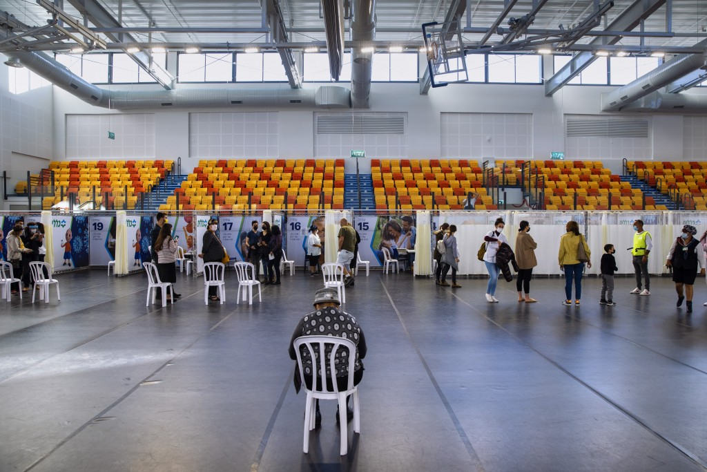Israelis line up to receive a Pfizer-BioNTech COVID-19 vaccine at a coronavirus vaccination center set up at a gymnasium in Petah Tikva, Israel, durin...