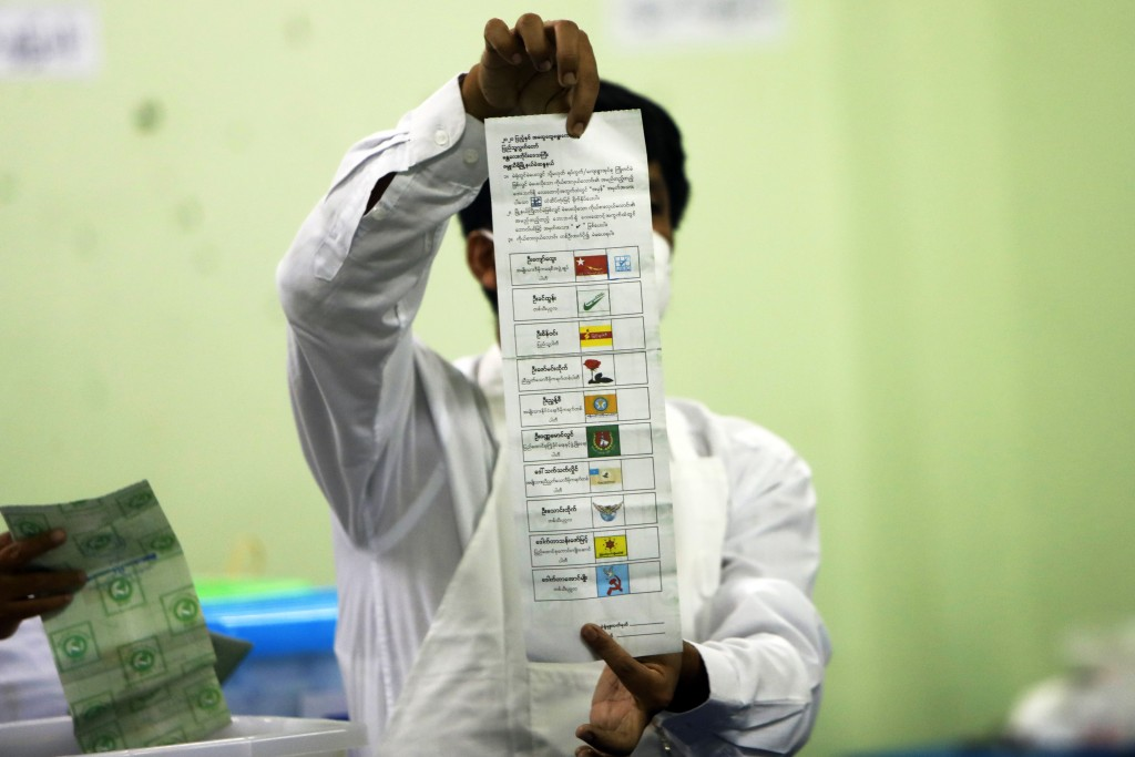 FILE - In this Sunday, Nov. 8, 2020 file photo, an official of the Union Election Commission counts ballots at a polling station in Naypyitaw, Myanmar...