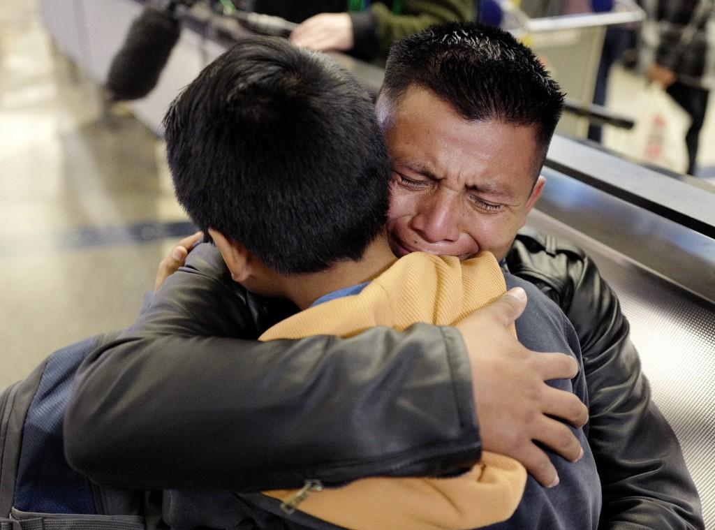 FILE - In this Jan. 22, 2020 file photo, David Xol-Cholom of Guatemala hugs his son, Byron, at Los Angeles International Airport as they reunite after...