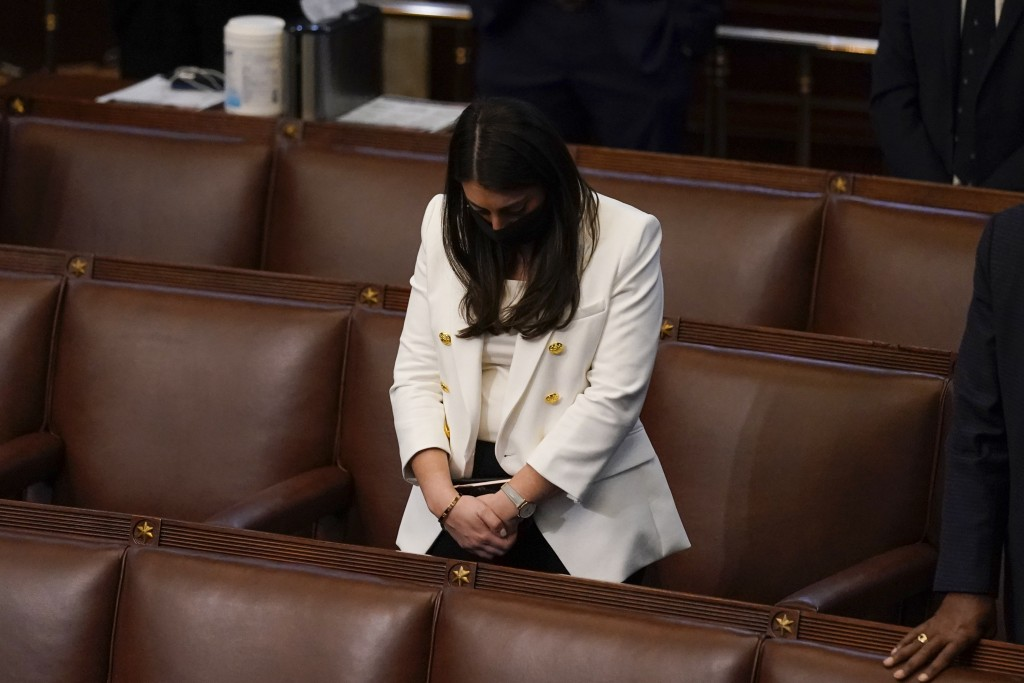 FILE - In this early Thursday, Jan 7, 2021 file photo, Rep. Alexandria Ocasio-Cortez, D-N.Y., bows her head during a closing prayer of a joint session...