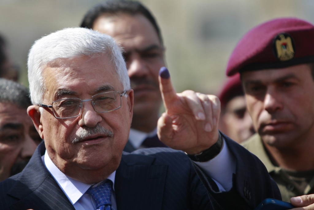 File - In this Saturday, Oct. 20, 2012 file photo, palestinian President Mahmoud Abbas shows his ink-stained finger after casting his vote during loca...