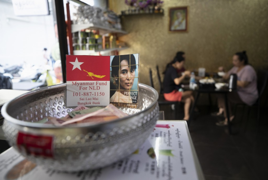 A donation bowl with an image of deposed Myanmar leader Aung San Suu Kyi is displayed on a stand as customers dine at Mandalay Food House in Bangkok, ...
