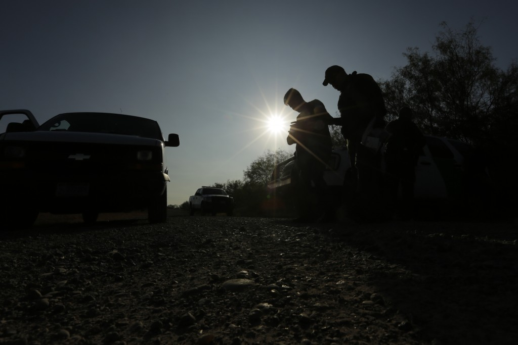 FILE - In this Nov. 6, 2019, file photo, Border Patrol agents stop men thought to have entered the country illegally, near McAllen, Texas, along the U...
