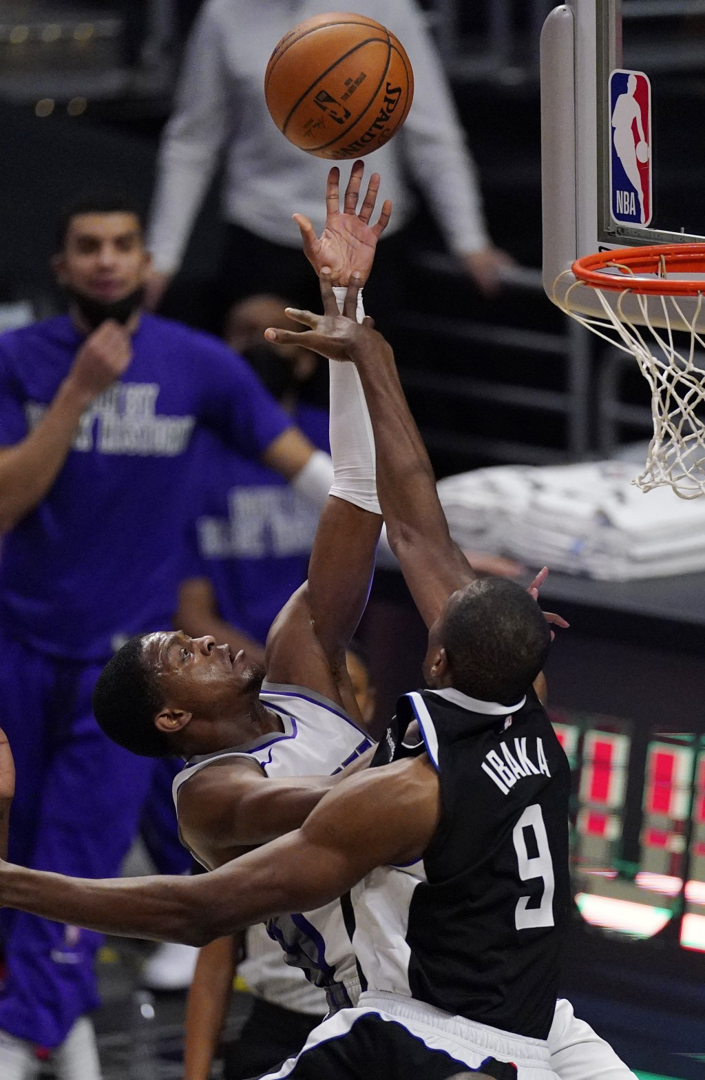 Sacramento Kings guard De'Aaron Fox, left, shoots as Los Angeles Clippers center Serge Ibaka defends during the first half of an NBA basketball game S...