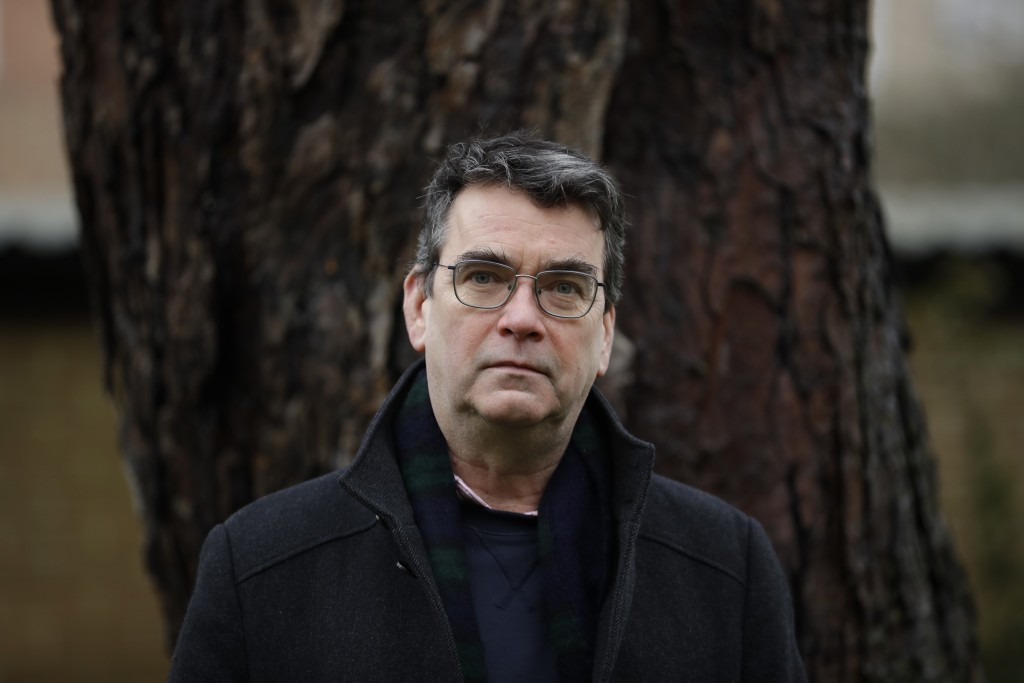 British novelist Mick Herron, the author of the Slough House espionage series, poses for photographs outside his home in Oxford, England, Wednesday, J...