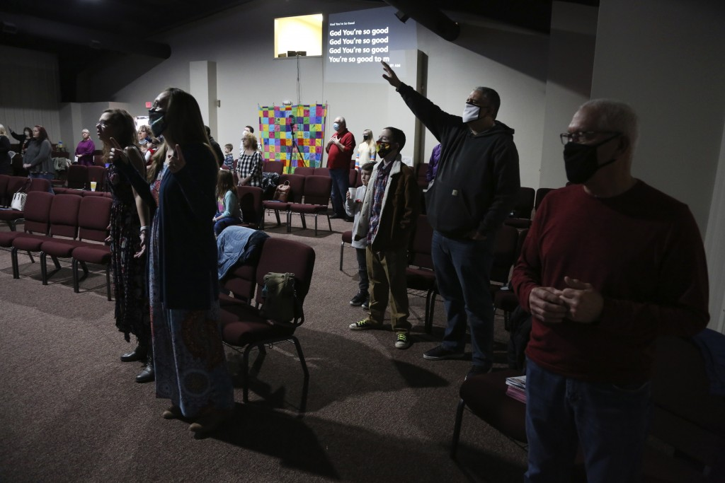 Travis Lowe, second from right, pastor of Crossroads Church in Bluefield, W.Va., raises his arm during services Sunday Jan. 23, 2021. Lowe, who has ex...