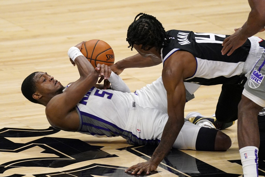 Sacramento Kings guard De'Aaron Fox, left, and Los Angeles Clippers guard Terance Mann grapple for a loose ball during the first half of an NBA basket...