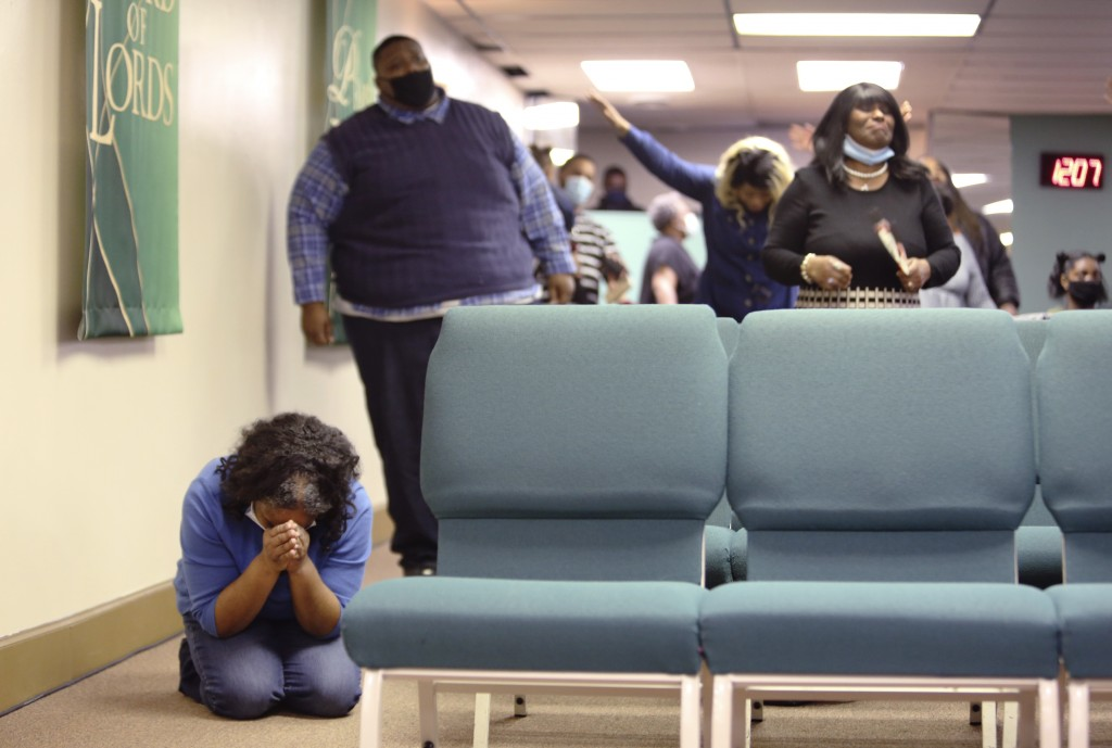 Constance Law falls to her knees in worship and prayer during Faith Center Church's first in-person service in two months in Bluefield, W.Va, on Satur...