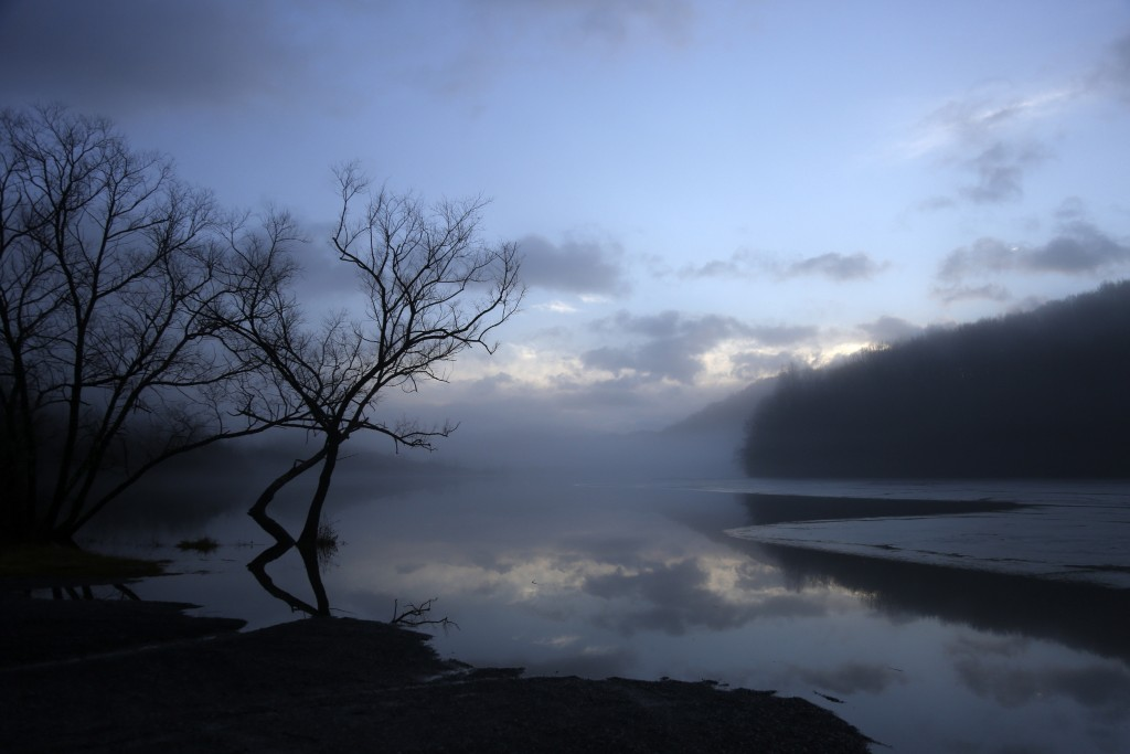 Clouds are reflected on a lake at dawn in Bluefield, W.Va, on Tuesday, Jan. 26, 2021. Members of three congregations in a small city in West Virginia'...