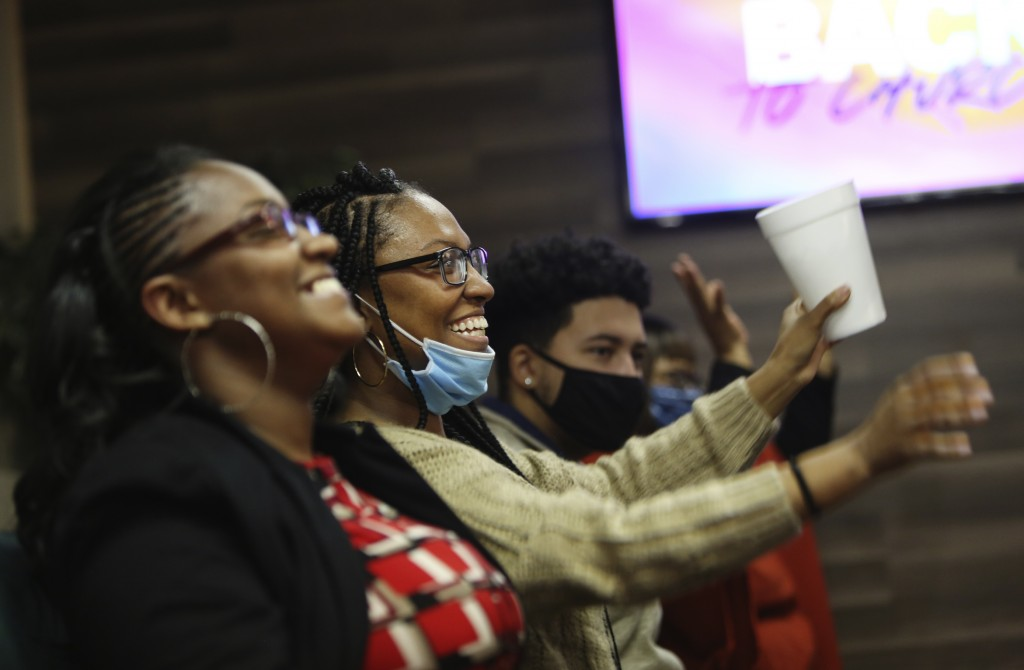 Sisters Shawnetta Lane, left, and Angenetta Lane, center, smile as they listen to Frederick Brown, pastor of Faith Center Church in Bluefield, W.Va., ...