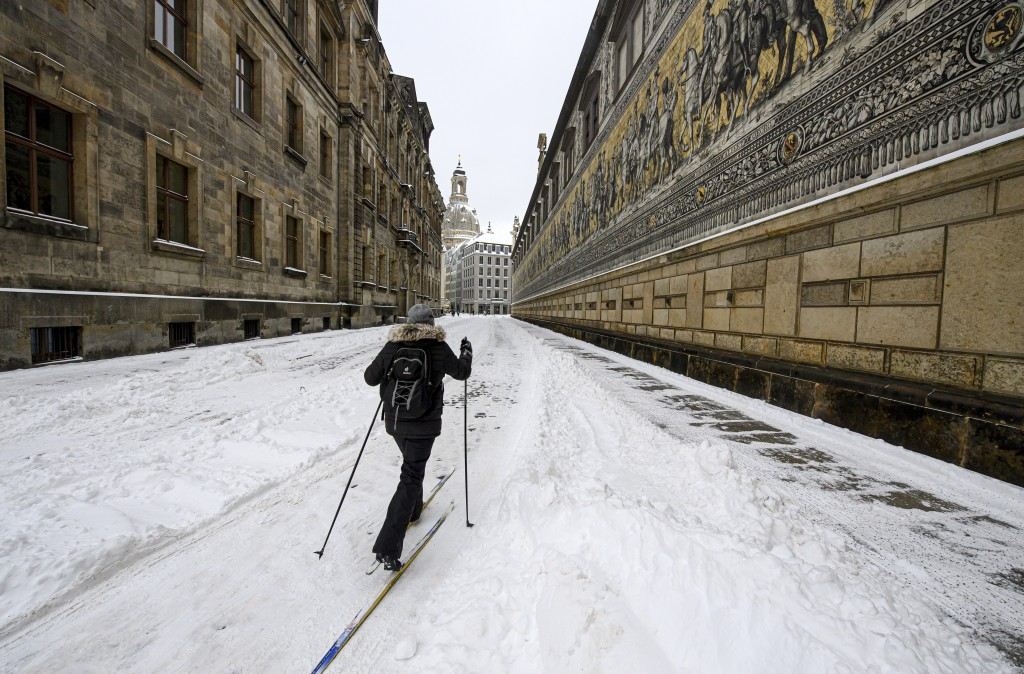 A woman uses cross-country skis as she walks through the old city of Dresden in Germany. Parts of Germany hit by strong winter weather. (Robert Michae...