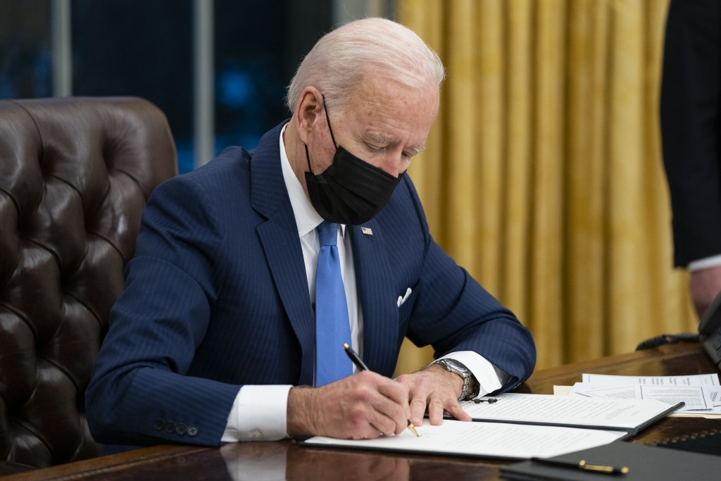 FILE - In this Feb. 2, 2021, file photo President Joe Biden signs an executive order on immigration, in the Oval Office of the White House in Washingt...