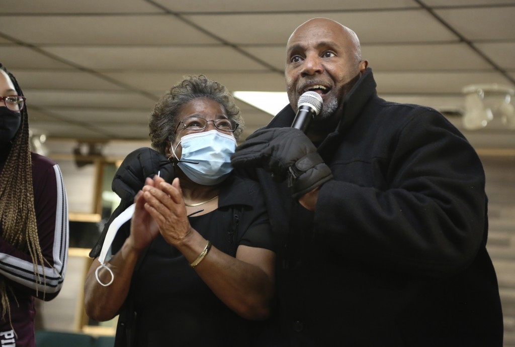Patricia Banks, center, claps while being hugged by Frederick Brown, pastor of Faith Center Church in Bluefield, West Va., on Saturday, Jan. 24, 2021....