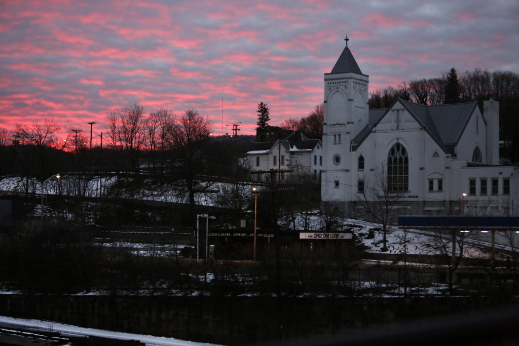 The sky lights up at dawn behind First Presbyterian Church and the rail yard in the historic coal city of Bluefield, W.Va, on Saturday, Jan. 24, 2021....