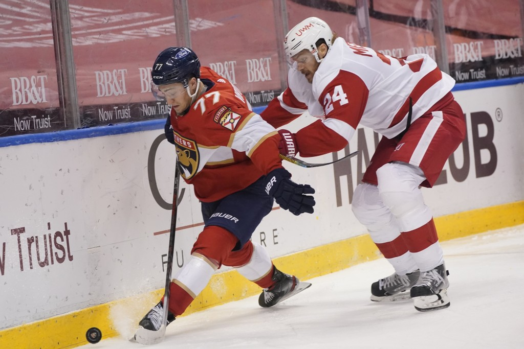 Florida Panthers center Frank Vatrano (77) and Detroit Red Wings defenseman Jon Merrill (24) battle for the puck during the second period of an NHL ho...