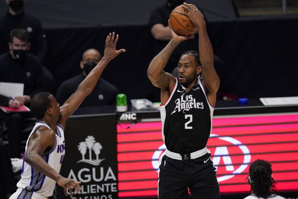 Los Angeles Clippers forward Kawhi Leonard, right, shoots as Sacramento Kings forward Harrison Barnes defends during the first half of an NBA basketba...
