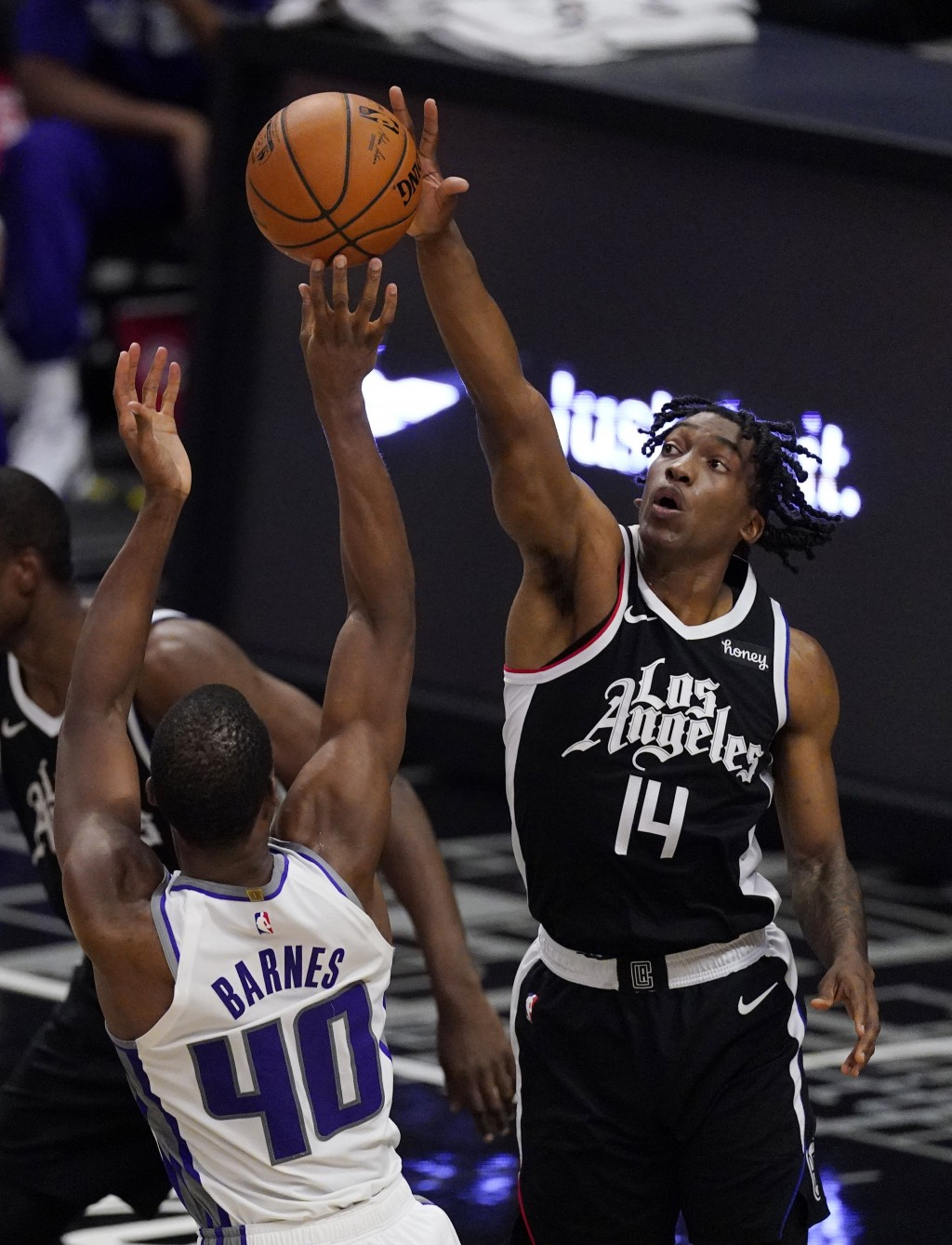Sacramento Kings forward Harrison Barnes, left, shoots as Los Angeles Clippers guard Terance Mann defends during the first half of an NBA basketball g...