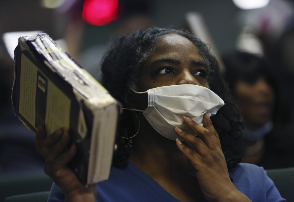 Constance Law holds a bible and a face mask as she worships with fellow congregants in Bluefield, W.Va, on Saturday, Jan. 24, 2021. (AP Photo/Jessie W...