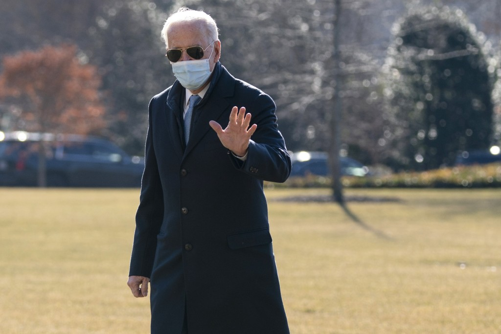 President Joe Biden waves to reporters as he arrives on the South Lawn of the White House, Monday, Feb. 8, 2021, in Washington. (AP Photo/Evan Vucci)