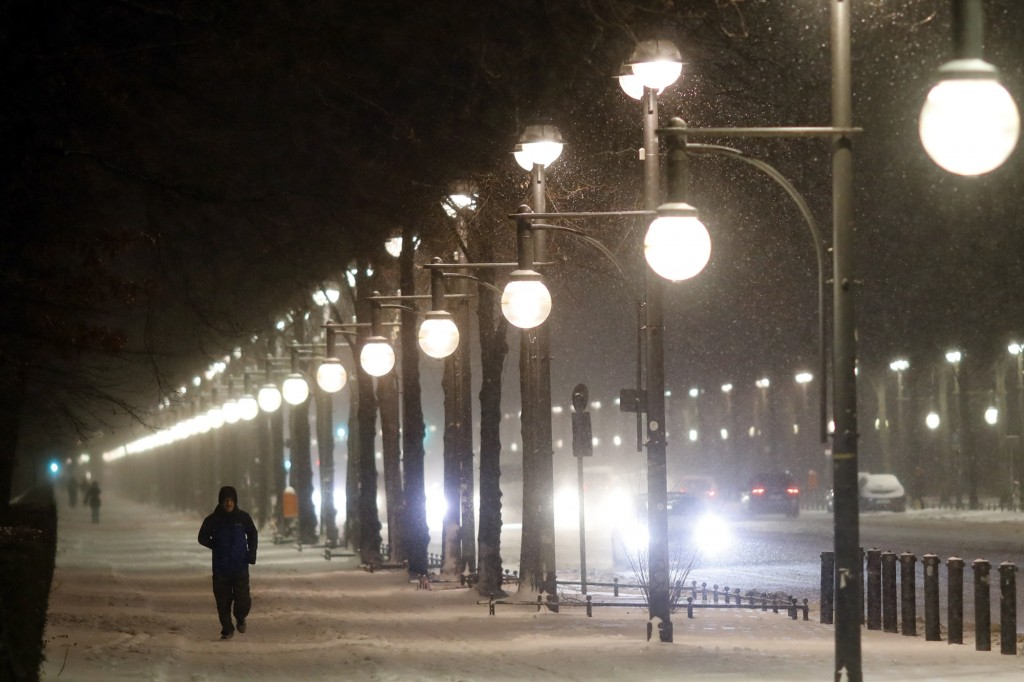 People walk on the snow covered boulevard 'Strasse des 17. Juni' in central Berlin, Germany, Monday, Feb. 8, 2021.Parts of Germany hit by strong winte...