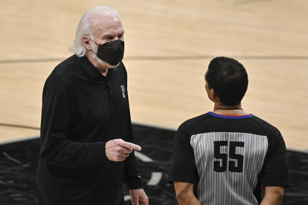 San Antonio Spurs head coach Gregg Popovich, left, talks to referee Bill Kennedy during the second half of an NBA basketball game against the Golden S...