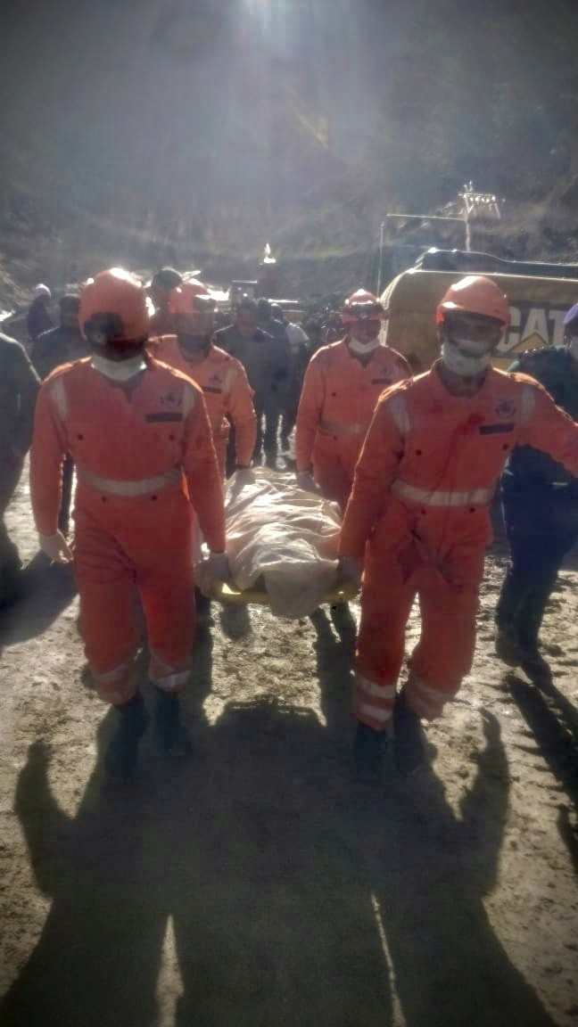 This photograph provided by National Disaster Response Force (NDRF) shows NDRF personnel carry a dead body recovered from debris after a portion of th...