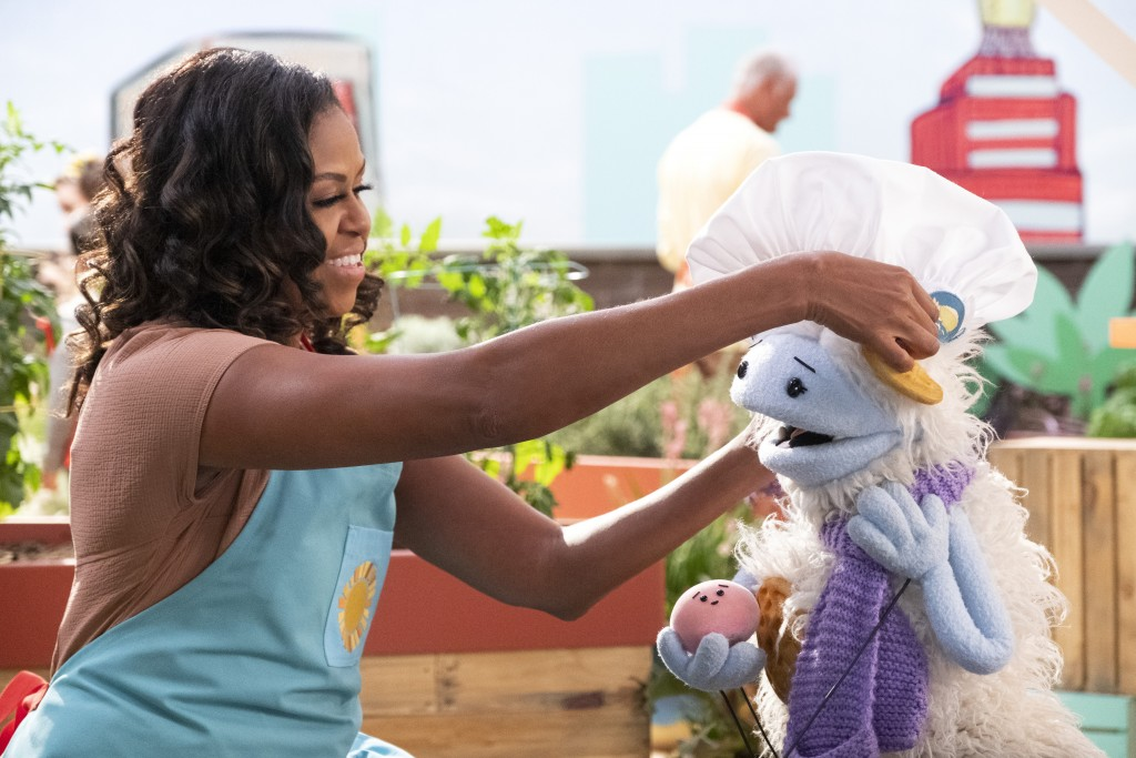 This image released by Netflix shows former first lady Michelle Obama putting a chef's hat on Waffles, a furry puppet with waffle ears and holding Moc...