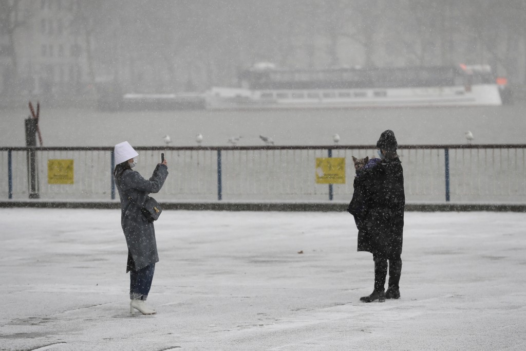 A woman takes pictures during a snow flurry as temperatures dropped below freezing during the third coronavirus lockdown in London, Tuesday, Feb. 9, 2...