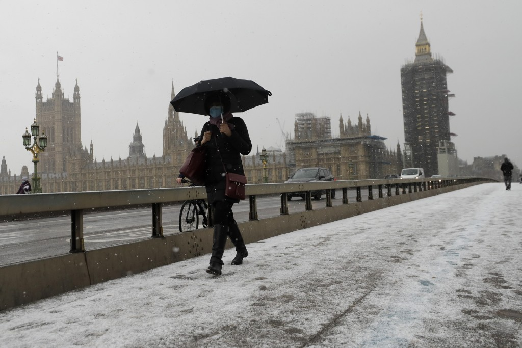 A woman walks over Westminster Bridge as temperatures dropped below freezing during the third coronavirus lockdown in London, Tuesday, Feb. 9, 2021. (...