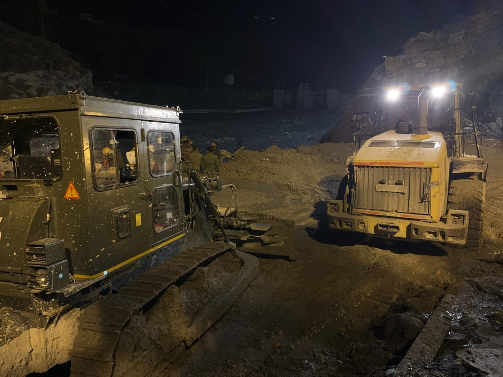 Indo Tibetan Border Police (ITBP) personnel using heavy machinery to clear debris as they try to rescue more than three dozen power plant workers trap...