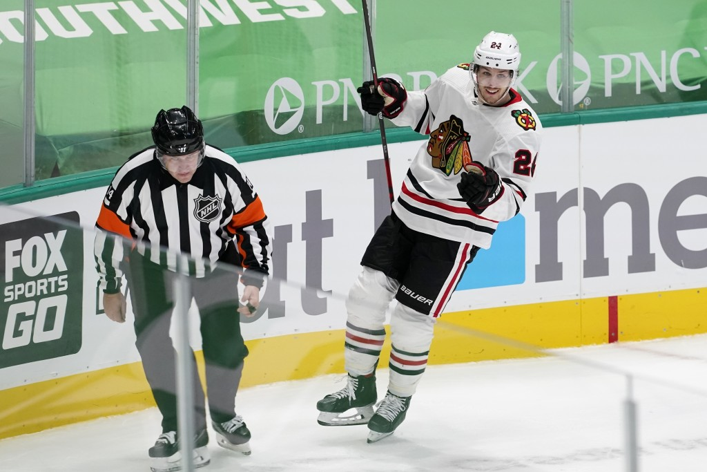 An official looks on as Chicago Blackhawks' Pius Suter celebrates his goal in overtime of an NHL hockey game against the Dallas Stars in Dallas, Tuesd...