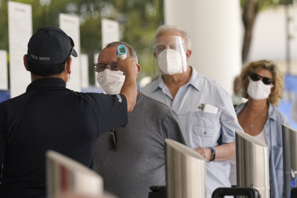 FILE - In this Feb. 8, 2021, file photo, Florida seniors have their temperatures taken before receiving the second dose of the Pfizer COVID-19 vaccine...