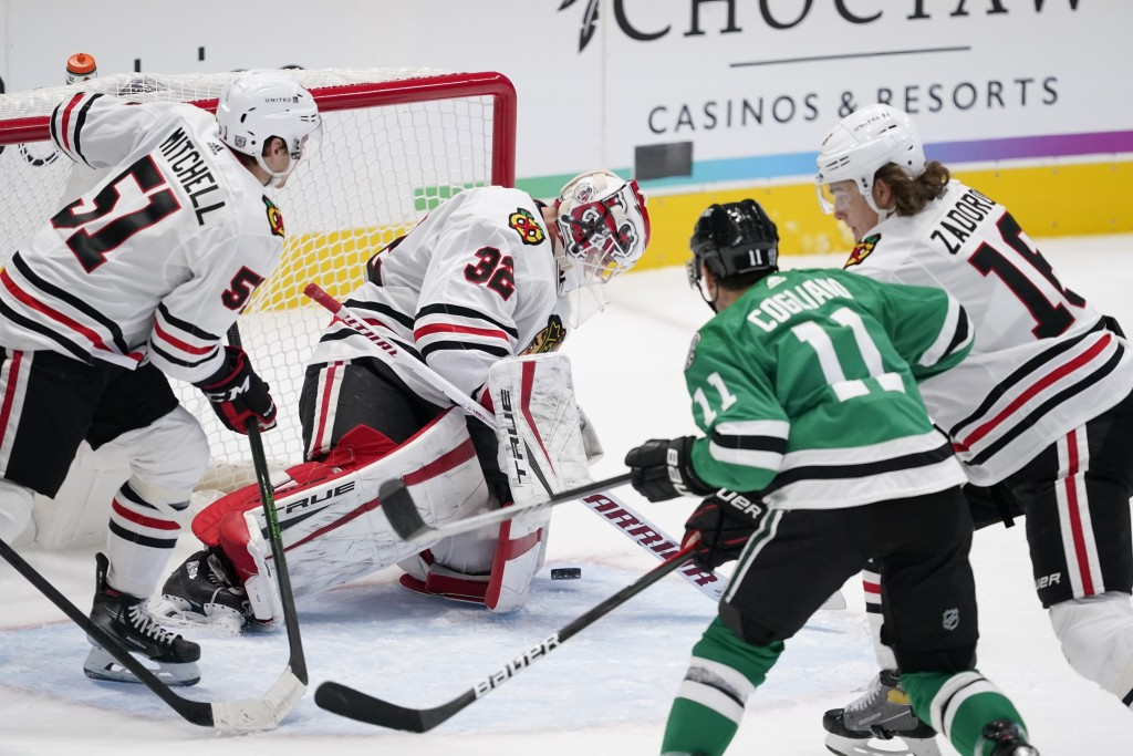 Chicago Blackhawks' Ian Mitchell (51) and Nikita Zadorov (16) help goaltender Kevin Lankinen (32) defend against a shot and pressure from Dallas Stars...