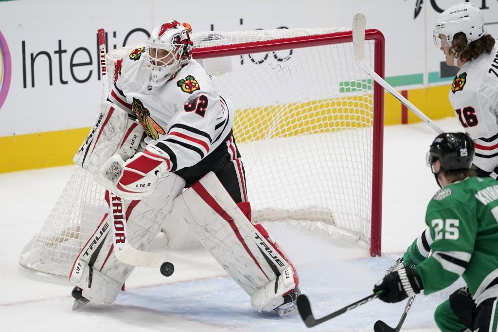 Chicago Blackhawks goaltender Kevin Lankinen (32) blocks a shot as Dallas Stars' Joel Kiviranta (25) pressures the net in the first period of an NHL h...