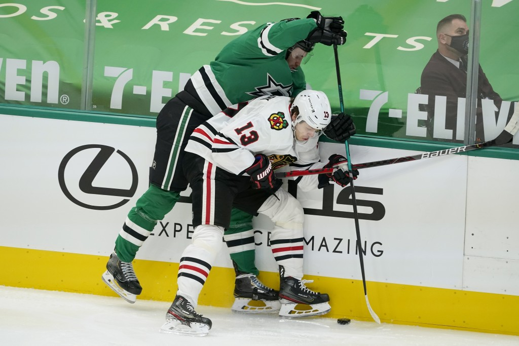 Chicago Blackhawks' Mattias Janmark (13) and Dallas Stars' Radek Faksa, left, compete for control of the puck in the first period of an NHL hockey gam...